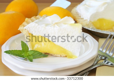 Close up of a slice of lemon meringue pie garnished with fresh mint leaves.  In the background there is lemons and the pie that the slice came from. - stock photo