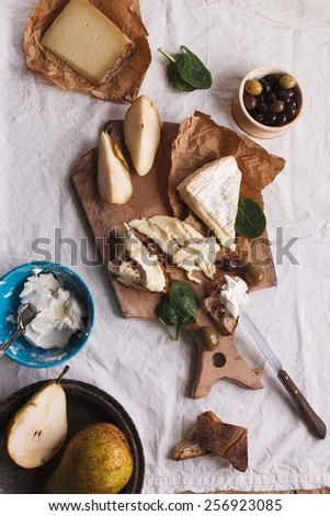 Close-up of a slice of wholemeal bread with variety cheeses and butter with sliced organic pear and rustic knife. Served on a dark rustic wooden table, on a napkin natural. Antipasti food concept. - stock photo