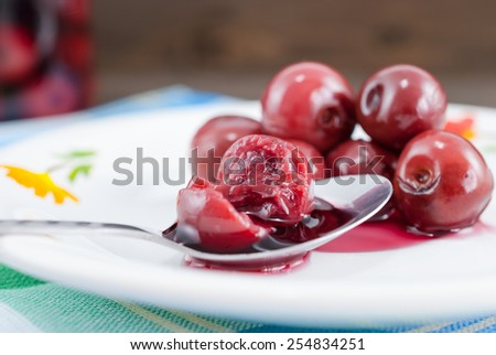 Close up of a sliced sour cherry on spoon along with other sour cherries taken out from a jar with compote - stock photo