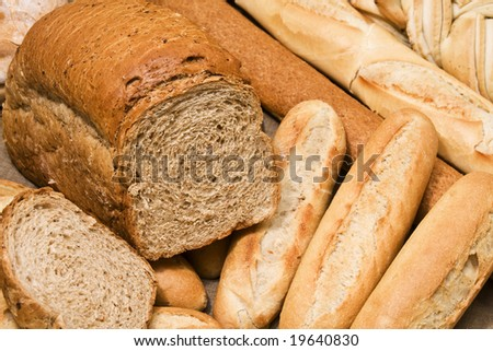 Close up of a sliced whole grain bread and baguettes. Focus on brown bread. - stock photo