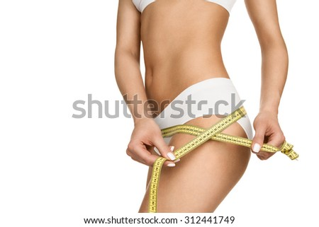 Close up of a slim woman measuring her hips isolated on white background - stock photo