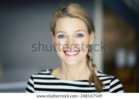 Close up Of A Smiling blond woman wearing a striped shirt - stock photo