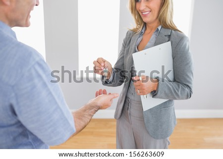 Close up of a smiling blonde realtor delivering a key to a buyer mature customer standing in an empty room - stock photo