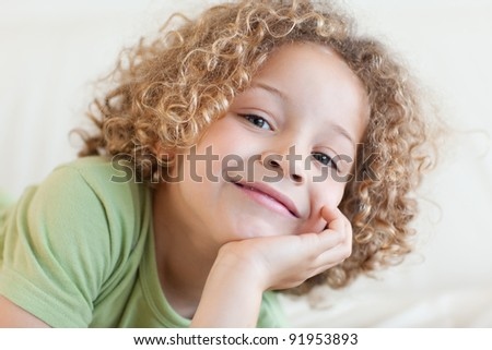 Close up of a smiling boy lying on a sofa while looking at the camera - stock photo