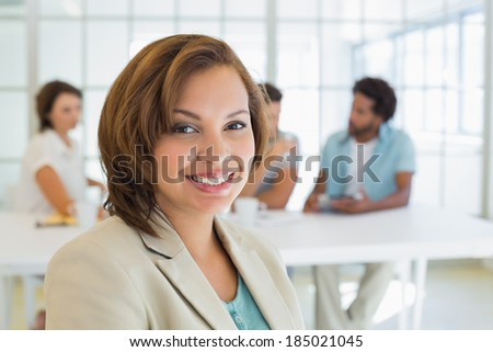 Close-up of a smiling businesswoman with colleagues in meeting in background at the office - stock photo