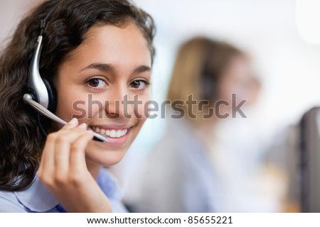 Close up of a smiling customer assistant wearing a headset - stock photo