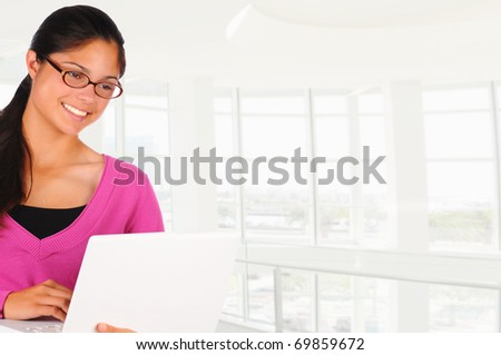 Close up of a smiling female teenage student with long brown hair holding a laptop computer in modern school building. Brunette girl wearing eye glasses in vertical format. - stock photo