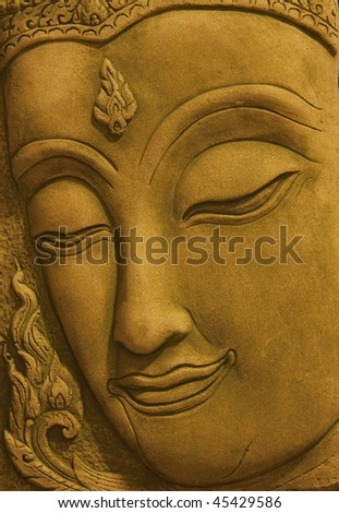 Close up of a smiling golden face sleeping Buddha statue with eyes closed - stock photo