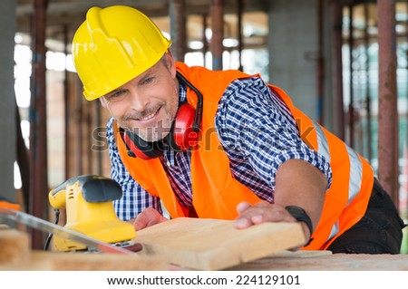 Close-up Of A Smiling Male Carpenter Looking At Wooden Plank At Construction Site - stock photo