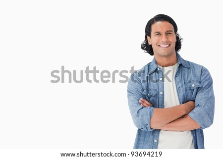 Close-up of a smiling man crossing his arms against white background - stock photo