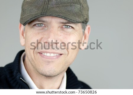 Close-up of a smiling man in a newsboy hat looking to camera. - stock photo