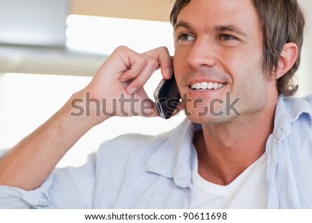 Close up of a smiling man making a phone call looking away from the camera - stock photo