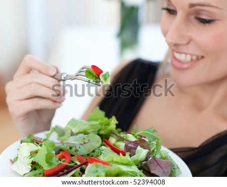 Close-up of a smiling woman eating a salad in the living-room - stock photo