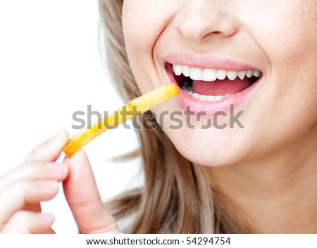 Close-up of a smiling woman eating fries isolated on a white background - stock photo