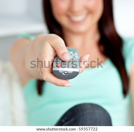 Close-up of a smiling woman hoding a remote in the living-room at home - stock photo