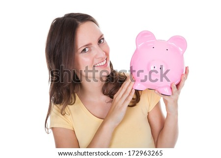 Close-up Of A Smiling Woman Holding Piggybank Over White Background