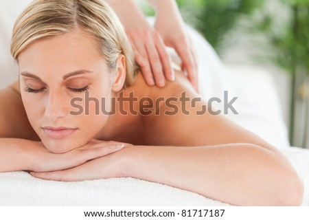 Close up of a smiling woman relaxing with eyes closed on a lounger during a massage in a wellness center - stock photo