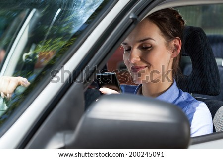 Close-up of a smiling woman texting on mobile phone during driving a car - stock photo