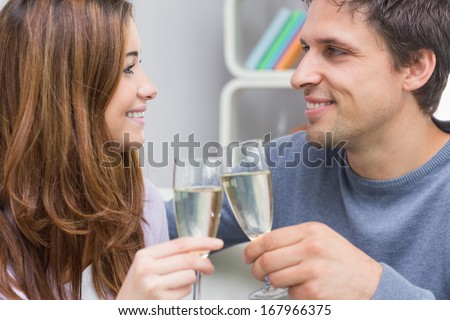 Close-up of a smiling young couple toasting flutes in the living room at home