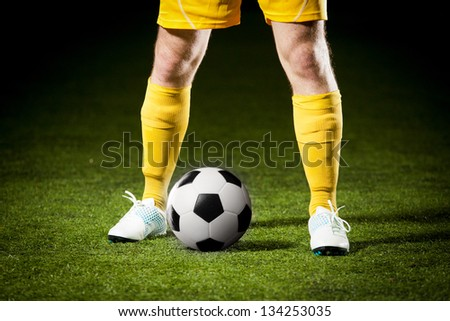 Close up of a soccer ball and a feet of a soccer player - stock photo