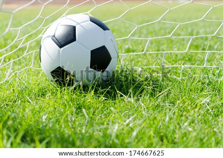Close-up of a soccer ball (football) going into  the goal with green background. - stock photo