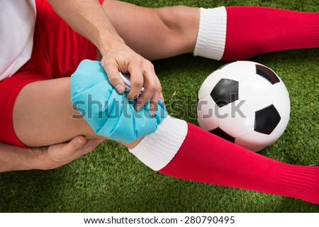 Close-up Of A Soccer Player Icing Knee With Ice Pack On Field - stock photo