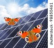 Close up of a solar energy panels and two butterflies. Environmental protection concept. - stock photo