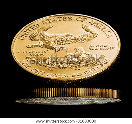 Close up of a solid gold eagle one ounce coin reflected in black shiny surface - stock photo