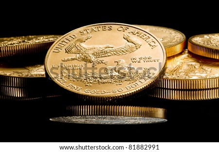Close up of a solid gold eagle one ounce coin stacked on other coins and reflected in black surface - stock photo
