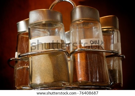 Close up of a spice rack with multiple spices labeled, with one blank label