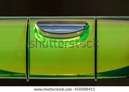 Close up of a spirit level  showing horizontal bubble against a dark background - stock photo