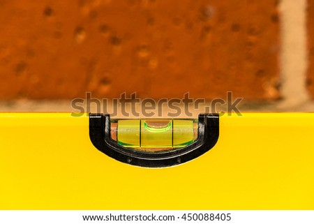 Close up of a spirit level  showing horizontal with shallow depth of focus against a brick wall - stock photo