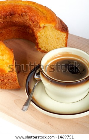 Close-up of a sponge cake with the cup of coffee and spoon on wood plate