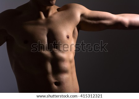 Close up of a sports man's chest. Muscular man on a dark background - stock photo