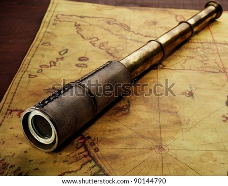 Close-up of a spyglass on the old map - stock photo