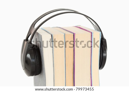 Close up of a stack of books and headphones against a white background - stock photo