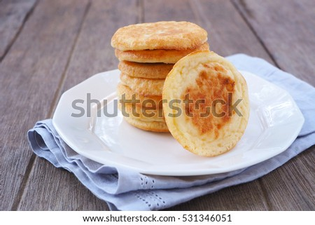 Close up of a stack of mini pancakes on a wooden table.