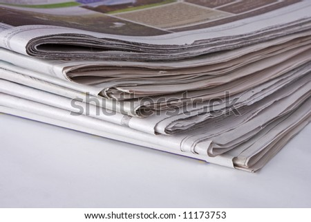 Close-up of a stack of newspapers, focusing on the bottom corner.