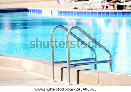 Close up of a stair rail in a swimming pool - stock photo