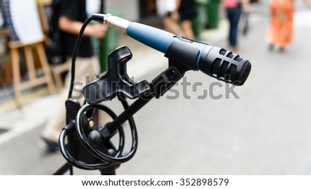 Close-up of a standing microphone in a street music performance with blurry motion people in background. Abstract musical instrument background on a street concert