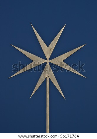 close up of a star shaped metal cross against a blue sky background.