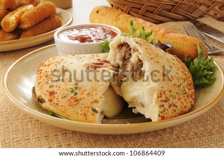 Close up of a steak and cheese calzone with mozzarella and bread sticks - stock photo