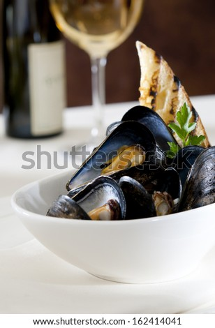 Close up of a steamed mussel appetizer with slice of toasted bread and white wine.