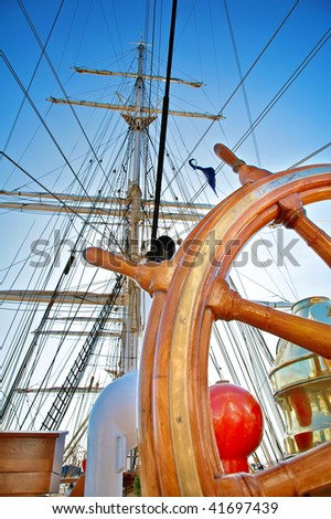 Close-up of a steering wheel against a mast of the sailing ship with focus on a mast - stock photo