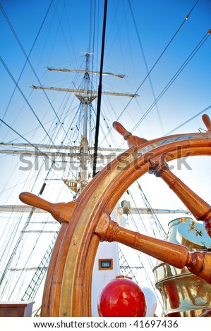 Close-up of a steering wheel against a mast of the sailing ship with focus on a wheel - stock photo