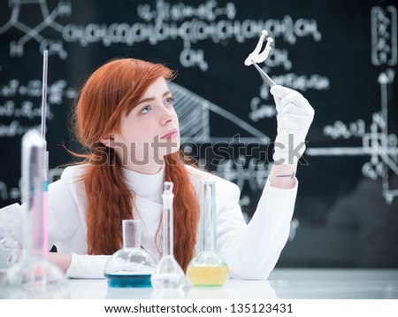 close-up of a student in a chemistry lab analyzing a bunch of mushrooms around a lab table with colorful liquids and a blackboard on the background