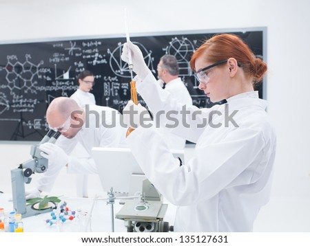 close-up of a student in chemistry lab conducting an experiment with colorful iquids and another three people analyzing data - stock photo