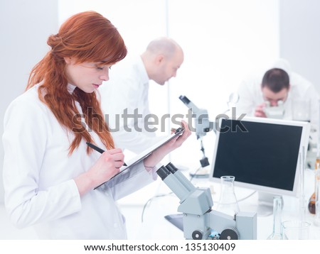 close-up of a student taking notes in a chemistry lab with another two scientists analyzing under microscope in the background around a lab table - stock photo