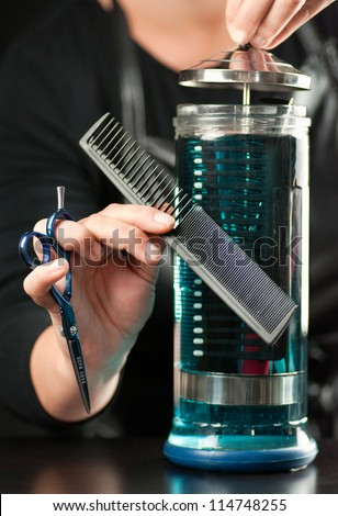 Close-up of a stylist putting a comb into clear glass container of disinfectant full of combs. - stock photo