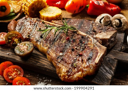 Close up of a succulent tender grilled porterhouse steak seasoned with pepper and rosemary on a wooden board with fresh halved tomatoes, mushrooms, corncobs and bell peppers - stock photo